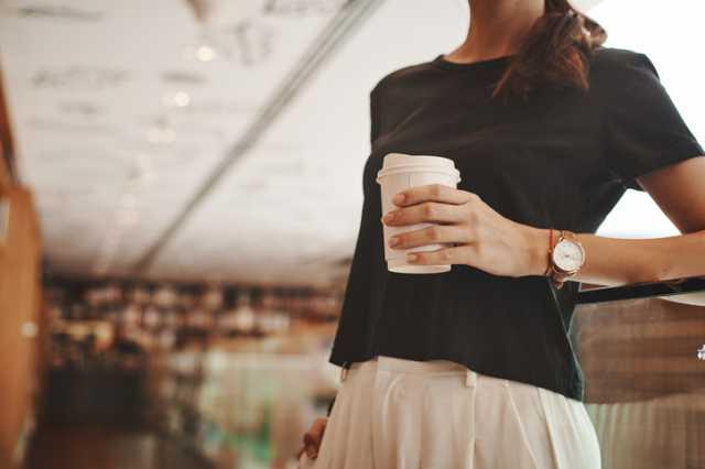 コーヒーを手に持つ女性