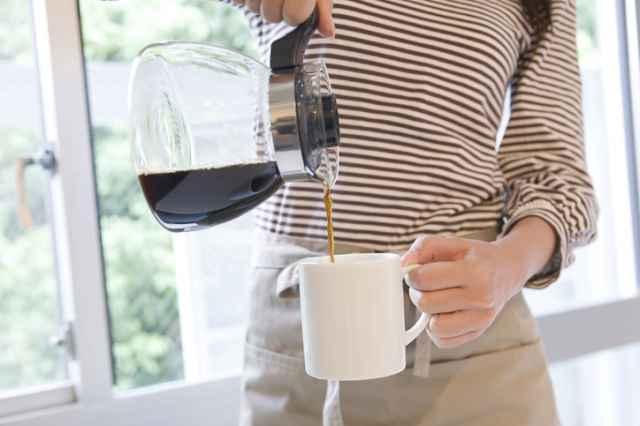 ポリフェノールたっぷりのコーヒーをカップに注ぐ女性