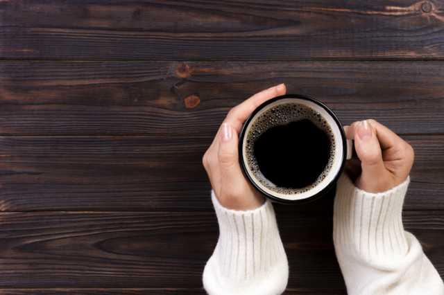 アメリカンコーヒーを手持つ人
