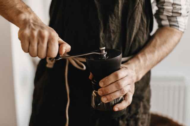 手動でコーヒー豆を挽く人