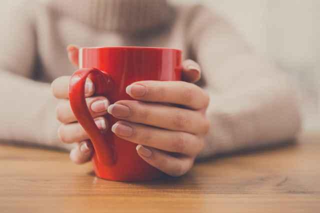 コーヒー入りマグカップを持つ人