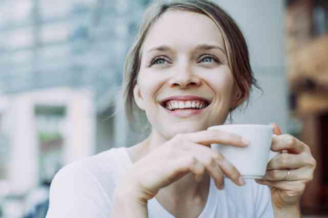 コーヒーを飲んで笑顔の女性