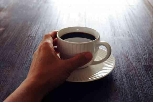 ブラックコーヒーを手に持つ