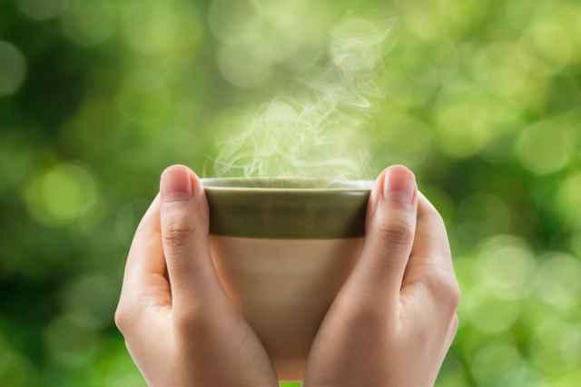 コーヒーマグカップを持つ手