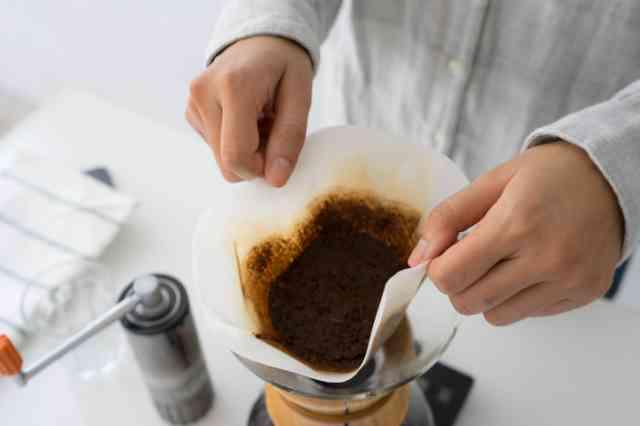 コーヒーかすを捨てようとする人