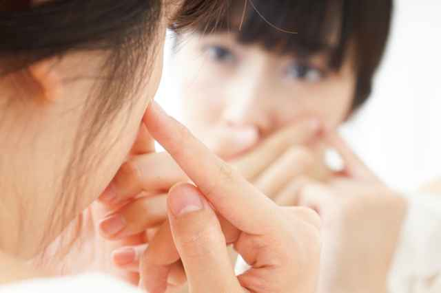 鏡で肌を気にする女性
