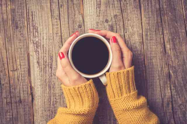 コーヒーカップを手に持つ