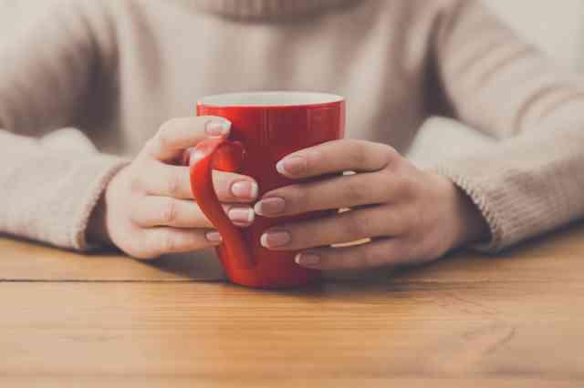 自宅でコーヒーカップを手に持つ人