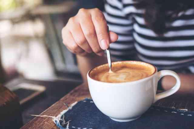 コーヒーにミルクと砂糖を入れて混ぜる人
