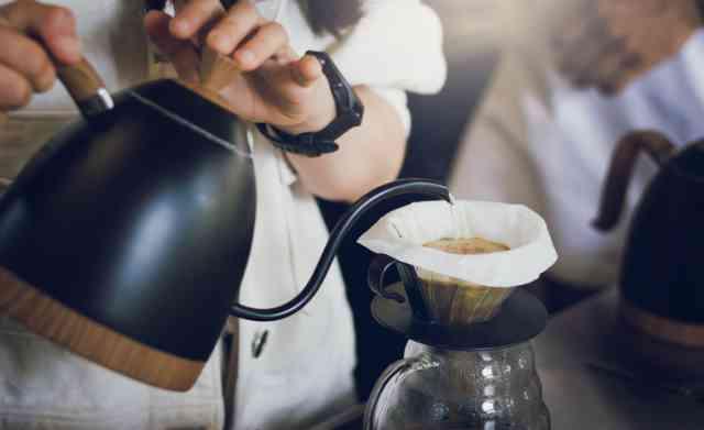 コーヒー抽出のために粉にお湯を注ぐ人