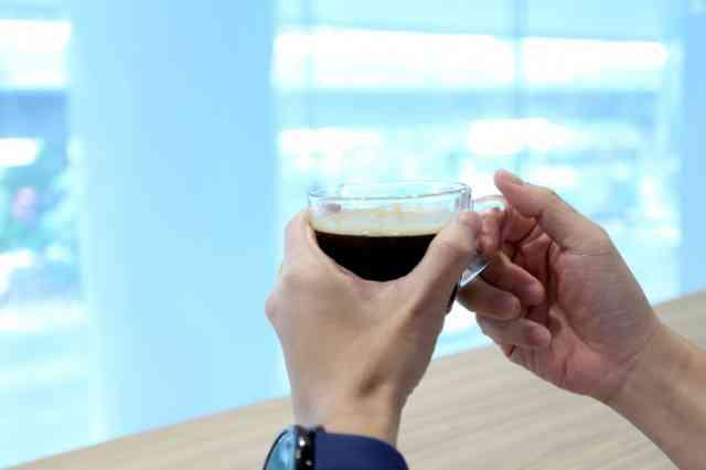 コーヒーを飲む人の手