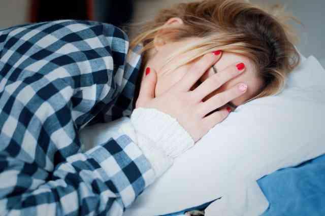 ベッドで頭痛にくるしむ女性
